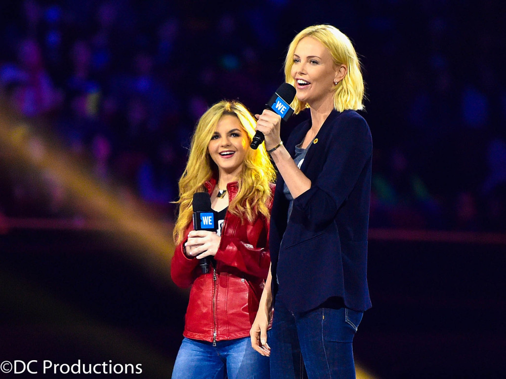 """INGLEWOOD, CA - APRIL 07: Activist Ashley Murphy (L) and actress Charlize Theron speak onstage at WE Day California 2016 at The Forum on April 7, 2016 in Inglewood, California. (Photo by Mike Windle/Getty Images for WE Day)"""