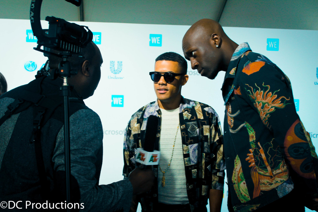 """INGLEWOOD, CA - APRIL 07: Channel A TV Founder Davies Chirwa talking to Artists Nico and Vinz during Red Carpet interviews at WE Day California 2016 at The Forum on April 7, 2016 in Inglewood, California."